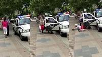 Aksi dua orang polisi Shanghai mendapat kecaman setelah membanting ibu yang menggendong balita. (Shanghiist))