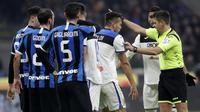 Wasit Gianluca Rocchi berdiskusi dengan para pemain Atalanta saat melawan Inter Milan pada laga Serie A di Stadion San Siro, Milan,Sabtu (11/1). Kedua klub bermain imbang 1-1. (AP/Luca Bruno)
