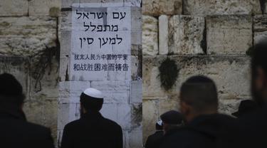 """Orang-orang Yahudi berdiri di depan poster dalam bahasa Ibrani dan Tiongkok mengatakan, """"Bangsa Israel berdoa untuk China."""" saat berdoa di Tembok Ratapan, situs paling suci di Kota Tua Yerusalem, Minggu, (16/2/2020). (AP Photo/Ariel Schalit)"""