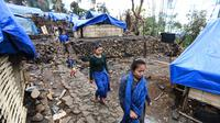 Sejumlah perempuan Suku Baduy Luar berjalan di lokasi bekas kebakaran Kampung Cisaban II, Desa Kanekes, Banten, Kamis (01/6). Warga Baduy Luar mulai membangun kembali rumah mereka yang terbakar beberapa waktu lalu. (Liputan6.com/Fery Pradolo)