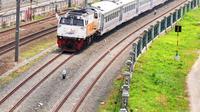 Kereta api melintas di jalur dwiganda atau double-double track (DDT) di kawasan Cipinang, Jakarta, Jumat (12/4). DDT segmen Jatinegara-Cakung mulai digunakan pada hari ini. (Liputan6.com/Herman Zakharia)