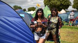 Dua wanita keluar dari tenda selama Festival Glastonbury di Worthy Farm, Somerset, Inggris (30/6/2019). Festival Glastonbury merupakan festival musik paling populer di dunia yang berlangsung lima hari. (AFP Photo/Oli Scarff)