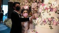 Pengantin memakai masker saat simulasi penerapan protokol kesehatan resepsi pernikahan di era new normal di Jakarta, Kamis (9/7/2020). Kegiatan ini bertujuan untuk mengedukasi masyarakat dalam acara pernikahan guna mencegah penyebaran COVID-19. (Liputan6.com/Faizal Fanani)