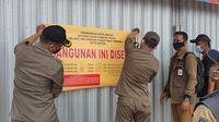 Satpol PP Kota Depok melakukan penyegelan minimarket di Jalan Raya Margonda. (Liputan6.com/Dicky Agung Prihanto)