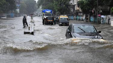 Sejumlah kendaraan melintasi banjir setelah hujan lebat di Mumbai, India (9/7). Mumbai dan daerah pinggiran lainnya telah mengalami hujan lebat semalaman yang mengakibatkan banjir. (AFP Photo/Indranil Mukherjee)