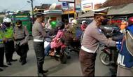 Petugas Satlantas Polres Tasikmalaya, Jawa Barat tengah membagikan selembaran termasuk masker kepada pengguna jalan, sebagai upaya sosialisasi larangan mudik 2021 yang disampaikan pemerintah pusat beberapa waktu lalu. (Liputan6.com/Jayadi Supriadin)
