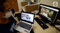 Seorang pria menyaksikan Menhub Budi Karya Sumadi memberikan keterangan melalui live streaming setelah Rapat Terbatas yang dipimpin Presiden Joko Widodo di Jakarta, Senin (27/4/2020). Budi Karya yang sudah sembuh dari covid-19 sedang menjalani isolasi mandiri di rumahnya. (merdeka.com/Dwi Narwoko)