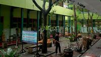 Pekerja membersihkan reruntuhan genting yang memenuhi halaman sekolah akibat gempa di SMK Negeri 1 Turen, Malang, Jawa Timur, Minggu (11/4/2021). Gempa yang mengguncang kawasan Malang dan sekitarnya membuat sejumlah bangunan rusak. (merdeka.com/Nanda F. Ibrahim)