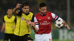 Olivier Giroud dihadang pemain Dortmund Sokratis pada Liga Champions Grup F antara Borussia Dortmund vs Arsenal di Dortmund,(6/11/2013).(AFP/Patrik Stollarz)