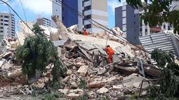 Petugas pemadam kebakaran mencari korban setelah sebuah bangunan runtuh di Fortaleza, negara bagian Ceara, Brasil, Selasa (15/10/2019). Hingga saat ini, penyebab runtuhnya rumah susun tujuh lantai tersebut masih belum diketahui. (LC Moreira/Futura Press via AP)