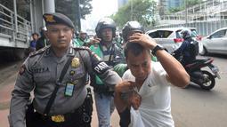 Terduga copet menutupi kepalanya dengan tangan saat akan diamankan menuju Mapolda Metro Jaya di Jalan Jenderal Sudirman, Jakarta (2/4). Polisi mengamankan tiga terduga copet. (Merdeka.com/Arie Basuki)