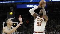 Aksi pemain Cleveland Cavaliers, LeBron James (23) melakukan tembakan melewati pemain Spurs, Danny Green (kiri) pada lanjutan NBA di basketball game di AT&T Center, San Antonio, (23/1/2018). Spurs menang 114—102. (AP/Eric Gay)