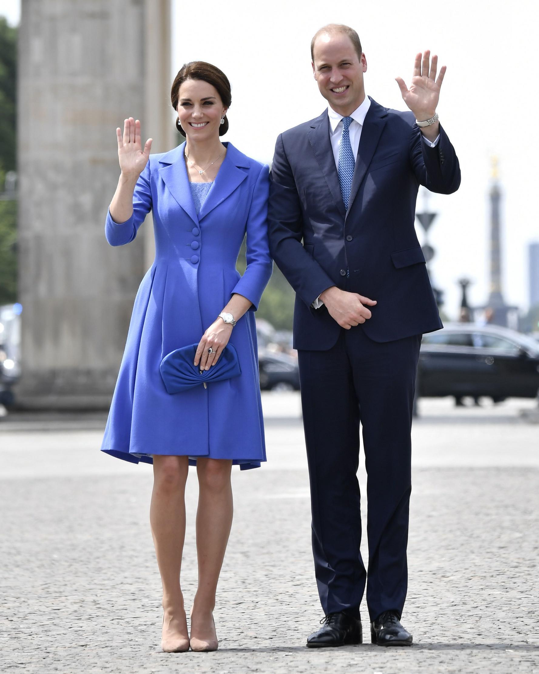 Pangeran William dan Kate Middleton melambaikan tangan sambil berpose di depan Gerbang Brandenburg di Berlin, Rabu (19/7). Pangeran William terlihat mengenakan setelan biru navy model klasik dan dasi biru untuk mengimbangi sang istri (John MACDOUGALL/AFP)