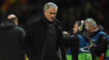 Pelatih Manchester United, Jose Mourinho berjalan sambil tertunduk usai pertandingan melawan Sevilla pada leg kedua babak 16 Liga Champions di Old Trafford, Inggris (13/3). MU kalah atas Sevilla 2-1. (AFP Photo/Oli Scarff)
