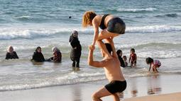 Sejumlah wanita muslim terlihat di Pantai Laut Mediterania, Tel Aviv, Israel pada 22 Agustus 2016. Saat pengunjung pantai mengenakan busana yang minim mereka tetap mengenakan jilbab dan busananya. (REUTERS / Baz Ratner)