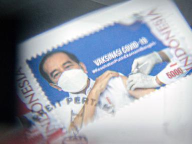 Perangko seri vaksinasi COVID-19 ditunjukkan di Kantor Filateli, Jakarta, Jumat (26/2/2021). Kementerian Komunikasi dan Informatika meluncurkan perangko seri vaksinasi COVID-19 bergambar Jokowi berkemeja putih dan memakai masker sedang disuntik vaksin. (Liputan6.com/Faizal Fanani)