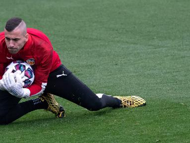 Kiper Valencia Jaume Domenech menangkap bola saat sesi latihan di Paterna Sports City, Paterna, Spanyol, Selasa (18/2/2020). Valencia akan menghadapi Atalanta pada leg pertama babak 16 besar Liga Champions di San Siro, 20 Februari 2020 dini hari WIB. (JOSE JORDAN/AFP)