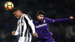 Bek Juventus, Alex Sandro (kiri) berebut bola udara dengan pemain Fiorentina, Gil Dias saat bertanding pada lanjutan Liga Serie A Italia di stadion Atemio Franchi, Florence (9/2). Juventus menang 2-0. (AFP Photo/Filippo Monteforte)