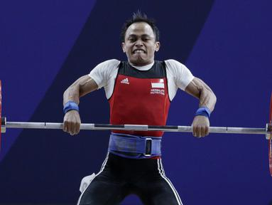 Lifter Suratman melakukan angkatan saat SEA Games 2019 cabang angkat besi nomor 55 kg di Stadion Rizal Memorial, Manila, Minggu (1/12). Dirinya meraih perak dengan total angkatan 250 kg. (Bola.com/M Iqbal Ichsan)