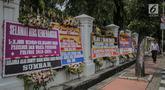Pejalan kaki melintasi karangan bunga bertuliskan ucapan selamat untuk Joko Widodo (Jokowi) dan Ma'ruf Amin di gedung Sekretariat Negara, Jakarta, Senin (22/4). Karangan bunga dari pendukung Jokowi-Ma'ruf tersebut ditujukan atas kemenangan pasangan itu pada Pilpres 2019. (Liputan6.com/Faizal Fanani)