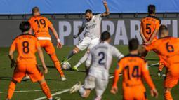 Striker Real Madrid, Karim Benzema, melepaskan tendangan saat melawan Valencia pada laga Liga Spanyol di Stadion Alfredo Di Stefano, Minggu (14/2/2021). Real Madrid menang dengan skor 2-0. (AP/Manu Fernandez)