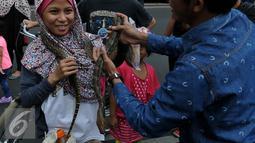 Pencinta reptil yang tergabung dalam Reptile dan Amphibian Community menampilkan beberapa hewan reptil mereka di Car Free Day, Jakarta, Minggu (23/8/2015). Kehadiran mereka menarik perhatian warga yang sedang menikmati CFD. (Liputan6.com/Johan Tallo)