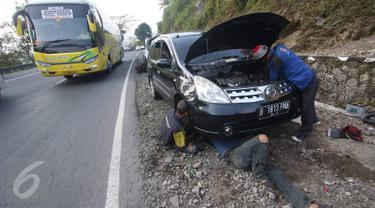 Montir memperbaiki mobil yang rusak di Jalan Warung Peuteuy, Garut, Jabar, Senin (4/7). Banyaknya kendaraan pemudik yang rusak menjadi berkah bagi para montir panggilan dengan pendapatan hingga 4x lipat dibanding biasa. (Liputan6.com/Immanuel Antonius)