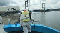 Penyemprotan disinfektan pada kapal penumpang pelabuhan Kendari oleh personil Polda Sultra untuk antisipasi Corona Covid-19.(Liputan6.com/Ahmad Akbar Fua)