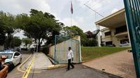 Seorang staf berjalan keluar memeriksa saat polisi Malaysia ditempatkan di depan Kedutaan Besar (Kedubes) Korea Utara di Kuala Lumpur, Selasa (7/3). Pemerintah Malaysia melarang staf Kedubes Korut keluar dari Negeri Jiran. (AP Photo/Vincent Thian)