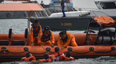 Personel Basarnas mengevakuasi korban selama simulasi penyelamatan pengungsi luar negeri di perairan Banda Aceh, Kamis (17/10/2019). Kegiatan diikuti peserta dari lintas stake holder terkait, termasuk unsur TNI, Polri, relawan dan pimpinan lembaga peduli bencana di Aceh. (CHAIDEER MAHYUDDIN/AFP)