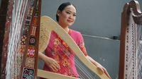 Musisi asal Bandung yang juga pemain harpa Frasisca Agustin menampilkan harpa bermotif Batik Kawung yang merupakan salah satu motif batik Jawa tertua. (Liputan6.com/Huyogo Simbolon)
