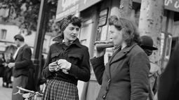 Dua wanita Paris, salah satunya makan roti lapis, menunggu untuk naik transportasi umum, pada Oktober 1944 di Paris, beberapa bulan setelah Pembebasan Paris, selama Perang Dunia Kedua. (AFP Photo)