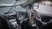 Pengemudi taksi daring, Aris Hardy Halim menyemprotkan disinfektan di dalam mobilnya di kawasan Bendungan Hilir, Jakarta, Jumat (8/5/2020). Pemasangan plastik pembatas  bertujuan untuk memberikan kenyamanan dan keamanan kepada pelanggan taksi daring. (Liputan6.com/Faizal Fanani)