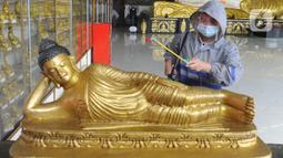 Umat menyemprotkan cairan disinfektan ke patung Buddha tidur di Vihara Buddha Dharma dan 8 Posat, Bogor, Jawa Barat, Minggu (7/2/2021). Ritual pencucian patung dan bersih-bersih ini dilakukan dalam rangka menyambut perayaan tahun baru China atau Imlek. (merdeka.com/Arie Basuki)