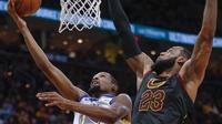Forward Golden State Warriors Kevin Durant (kiri) dihalangi bintang Cleveland Cavaliers LeBron James pada laga NBA 2017-2018 di Quicken Loans Arena, Senin (15/1/2018) atau Selasa (16/1/2018) WIB. (AFP/Michael Hickey)