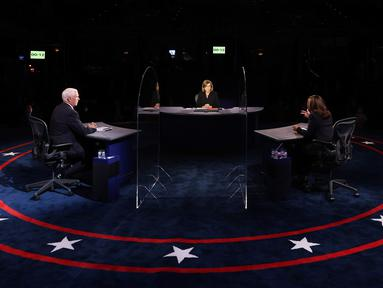 Wakil Presiden Mike Pence menyimak penantangnya, Senator Kamala Harris dari Partai Demokrat berbicara pada Debat cawapres Amerika Serikat di Kingsbury Hall, Universitas Utah di Salt Lake City, Rabu (7/10/2020).  Dalam debat, Pence dan Harris duduk dan diberi sekat kaca. (Justin Sullivan/Pool via AP)