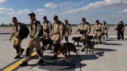 Anggota tim SAR Ceko beserta anjing pelacak berjalan menaiki pesawat di bandara Vaclav Havel di Praha, Rabu (5/8/2020). Republik Ceko mengirimkan sekitar 37 personel dan lima ekor anjing pelacak untuk membantu pencarian korban ledakan dahsyat di Beirut, Lebanon. (AP Photo/Petr David Josek)