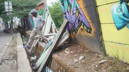 Seorang  pria melintas dekat tembok Jalan Juanda yang ambruk di kawasan Depok, Jawa Barat, Senin (2/12/2019). Kondisi tembok yang dipenuhi mural tersebut mulai rapuh dan sebagian sisinya telah ambruk serta miring sehingga membahayakan pejalan kaki. (Liputan6.com/Immanuel Antonius)