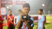 Pemain Terbaik Rusun Cup 2015 dari Rusun Daan Mogot, Mohammad Sobri, berpose dengan pialanya seusai laga final di Stadion Soemantri Brojonegoro, Jakarta, Minggu (8/11/2015). ( Bola.com/Nicklas Hanoatubun)