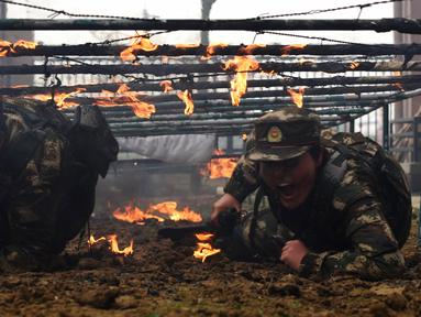 Tentara wanita China melewati rintangan api saat melakukan latihan militer jelang Hari Perempuan Internasional di Hefei, China (6/4). (AFP)