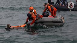 Anggota Tim SAR Gabungan saat mengevakuasi serpihan dari badan pesawat  Sriwijaya Air SJ 182 di perairan Kepulauan Seribu, Jakarta, Senin  (11/1/2021).  Pencarian tetap dilakukan baik untuk jenazah penumpang, serpihan potongan bagian pesawat terbang, maupun kotak hitam.  (merdeka.com/Arie Basuki)