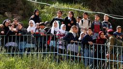Ekspresi anak-anak Palestina saat menyaksikan warga Yahudi merayakan Hari Purim di Jalan al-Shuhada, Kota Hebron, Tepi Barat, Kamis (1/3). Hari Purim dirayakan dengan parade dan pesta kostum. (AFP PHOTO/HAZEM BADER)