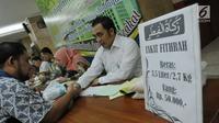 Petugas zakat melakukan ijab penerimaan zakat di Masjid Istiqlal, Jakarta, Jumat (1/7). Waktu pembayaran dibuka hingga malam takbiran dengan pembayaran zakat senilai Rp50ribu dan beras 3,5 liter. (Liputan6.com/Helmi Afandi)