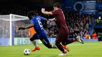 Pemain Barcelona, Luis Suarez berebut bola dengan pemain Chelsea, Victor Moses pada pertandingan leg pertama 16 besar Liga Champions di Stamford Bridge, Selasa (20/2). Barcelona ditahan imbang Chelsea dengan skor 1-1 (AP/Alastair Grant)