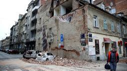 Gempa Terparah dalam 140 Tahun di Kroasia: Warga melewati bangunan yang rusak dan mobil-mobil hancur oleh puing-puing setelah gempa di jalan-jalan pusat kota Zagreb (22/3/2020).  Gempa magnitudo 5,3 ini tercatat sebagai yang terbesar, yang mempengaruhi Kroasia dalam 140 tahun. (AFP/Damir Sencar)