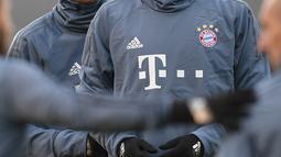 Bek Bayern Munchen, Mats Hummels dan striker Thomas Mueller tersenyum saat latihan di Munich, Jerman selatan (12/3). Bayern Munchen akan bertanding melawan wakil Inggris, Liverpool pada leg kedua babak 16 besar Liga Champions. (AFP Photo/Christof Stache)