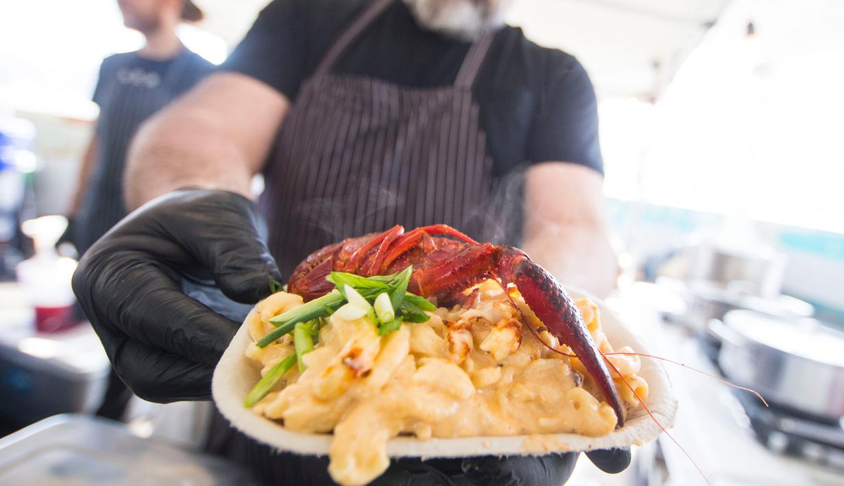 Penjual memperlihatkan kreasi masakannya yang diberi nama Crawfish Mac saat festival aneka makaroni keju bertajuk 2020 Mac and Cheese Festival di Mississauga, Kanada, 16 Februari 2020. Sebagai salah satu festival terbesar di jenisnya di Amerika Utara, ajang itu digelar tiga hari. (Xinhua/Zou Zheng)