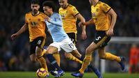 Gelandang Manchester City, Leroy Sane, berusaha melewati pemain Wolverhampton Wanderers pada laga Premier League di Stadion Etihad, Manchester, Senin (14/1). Manchester City menang 3-0 atas Wolverhampton Wanderers. (AP/Dave Thompson)