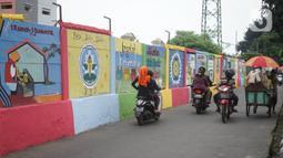 Pengguna jalan melintas di depan mural bertema Kota Jakarta di sekitar Rusunawa KS Tubun, Jakarta, Senin (23/11/2020). Mural tersebut dibuat guna memercantik lingkungan di sekitar rusun agar lebih berwarna dan tidak tampak kumuh. (Liputan6.com/Immanuel Antonius)