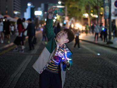 Seorang anak bersiap meluncurkan mainannya selama perayaan Chuseok di sebuah jalan di Seoul (5/10). Chuseok merupakan festival panen tahunan dan hari libur nasional selama seminggu di Korea Selatan. (AFP Photo/Ed Jones)